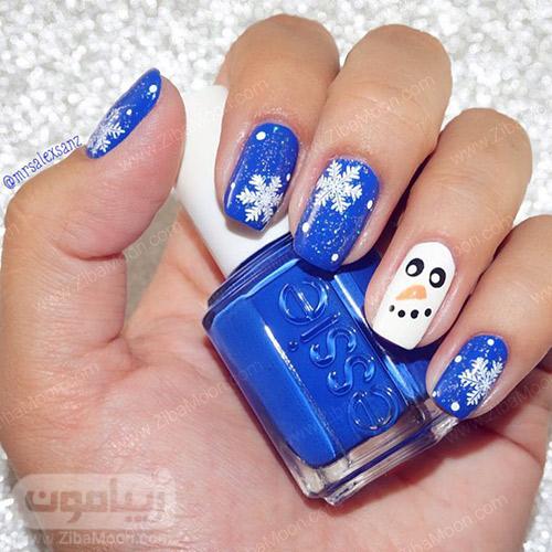 طراحی ناخن زمستانی با لاک آبی و طرح دانه های برف