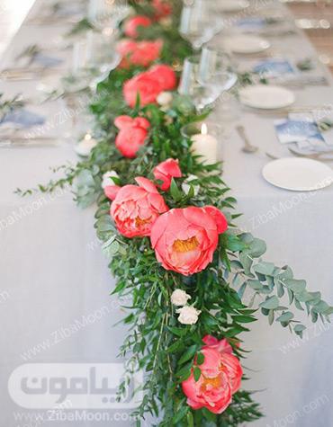 گل آرایی میز شام عروسی با گلهای مرجانی و برگهای سبز