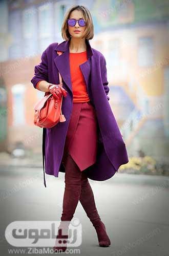 استایل زمستانی زنانه با بوت بلند آلویی، دامن صورنی، لباس مرجانی و پالتو بنفش
