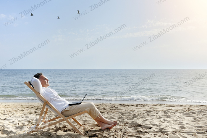 مرد دراز کشیده کنار دریا