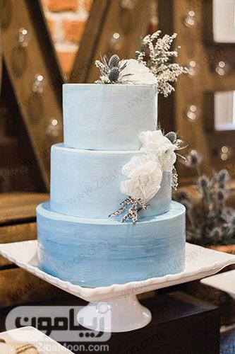 کیکی عروسی آبی رنگ با تزیین گلهای سفید