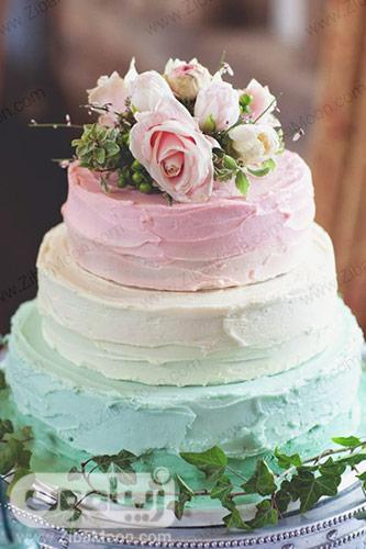 کیک عروسی سه طبقه با تزین صورتی سفید سبز نعنایی و گلهای طبیعی