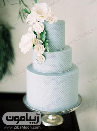 کیک سه طبقه با تزیین فوندانت آبی و گلهای سفید