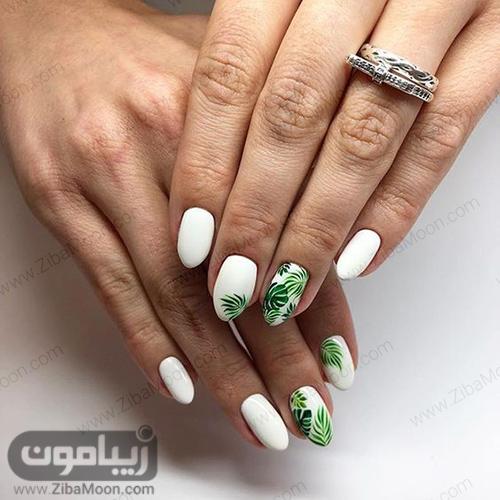 لاک ناخن سفید و طرح برگ سبز روی ان