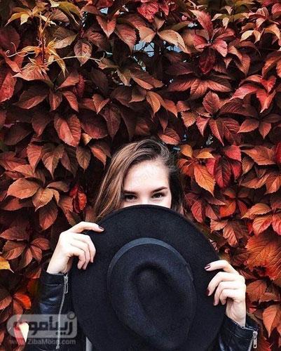عکس پروفایل دخترانه در کنار برگهای پاییزی با یک کلاه بزرگ